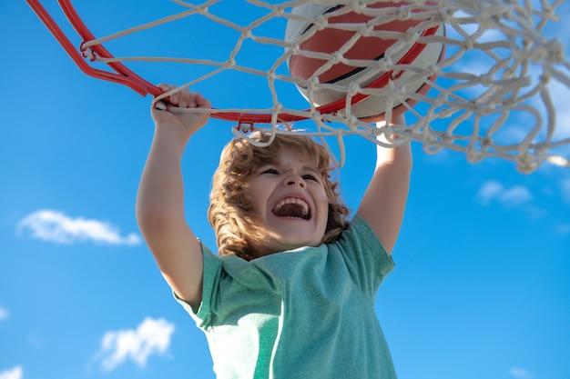Gracz koszykówki podbiega i zanurza piłkę