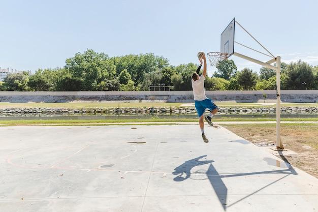Gracz koszykówki rzuca koszykówkę w obręczu