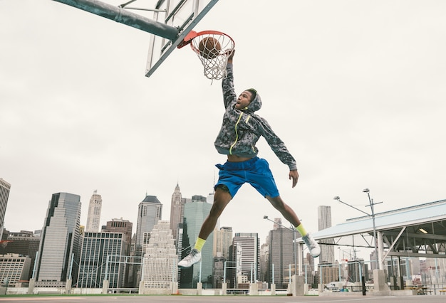 Gracz koszykówki wykonuje slamsy wsad na ulicznym sądzie.