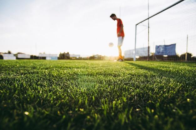 Gracz piłki nożnej na boisku piłkarskim trenuje przy zmierzchem