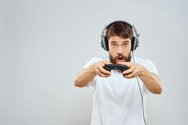 Gracz płci męskiej grający na konsoli z joystickami w słuchawkach