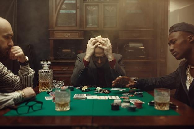 Gracz pokera wydaje wszystkie pieniądze w kasynie, ryzykuje. uzależnienie, dom hazardowy
