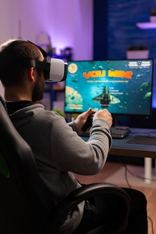 Gracz przegrywający kosmiczną strzelankę online z zestawem słuchawkowym do wirtualnej rzeczywistości. esport człowiek siedzi na krześle do gier późno w nocy w domowym studiu przy użyciu profesjonalnego sprzętu