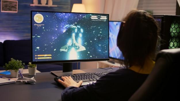 Gracz siedzi na fotelu do gier i zaczyna grać w kosmiczną strzelankę w profesjonalnym zestawie słuchawkowym. nowoczesne studio wyposażone w system rgb pulpit, klawiaturę, mysz, wykorzystujące technologię sieciową wirele