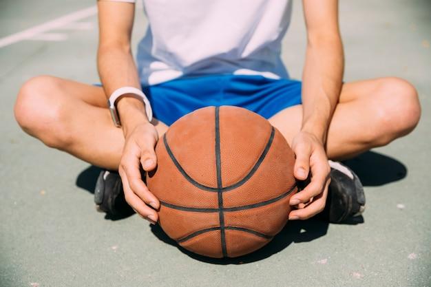 Gracz trzyma koszykówkę siedząc na placu zabaw