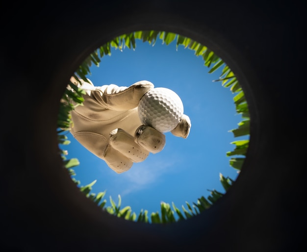 Gracz trzyma piłkę golfową. widok z wnętrza dziury