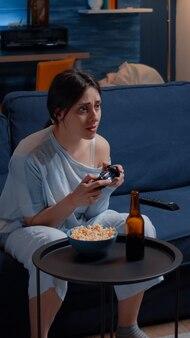 Gracz używający joysticka grający w gry wideo z joystickiem siedzącym na kanapie w salonie wygrywając zawody