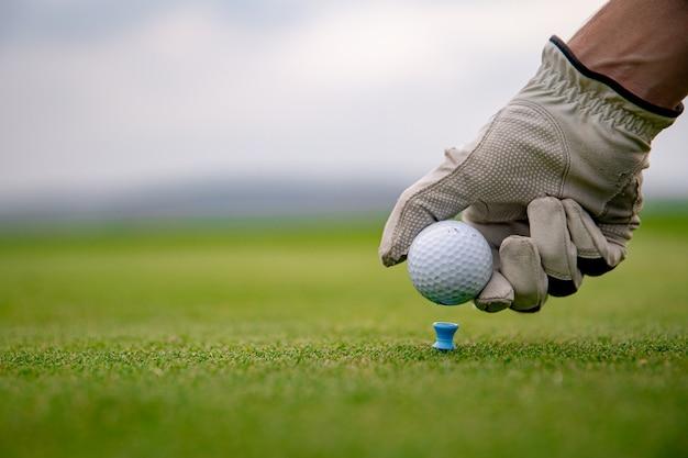 Gracz w golfa przygotowuje piłkę do wystrzelenia na polu golfowym