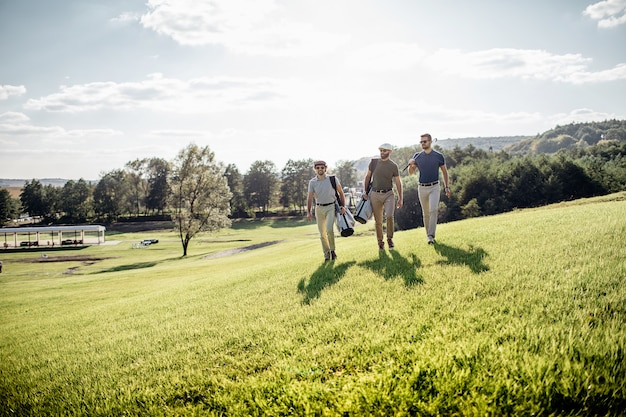 Gracz w golfa spacerujący i niosący torbę na kursie podczas letniej gry w golfa
