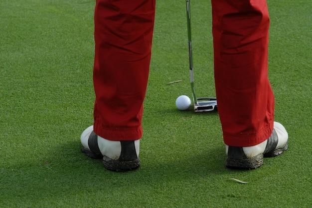 Gracz w golfa uderza piłkę przy putting green