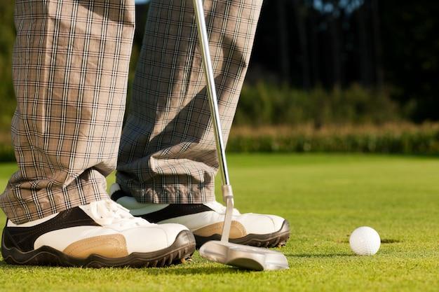 Gracz w golfa umieszcza piłkę w dziurze