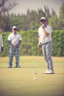 Gracz w golfa w putting green uderzając piłkę w otwór