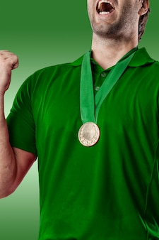 Gracz w golfa w zielonej koszuli świętuje ze złotym medalem, na zielonym tle.