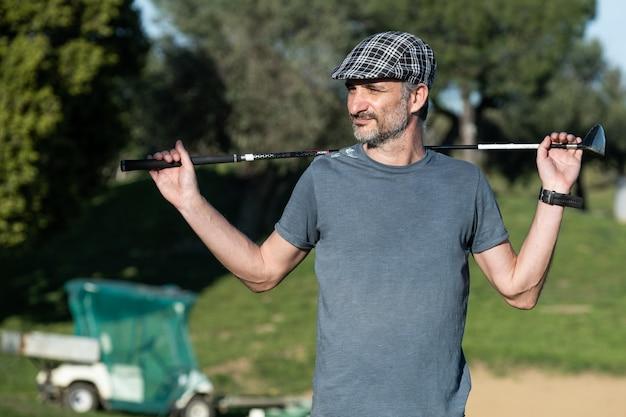 Gracz w golfa z czapką trzyma kij golfowy na plecach