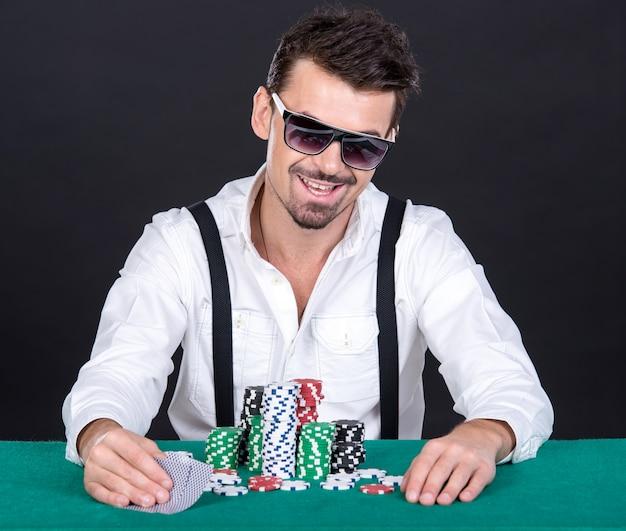 Gracz w pokera w czarnych okularach, w kasynie.