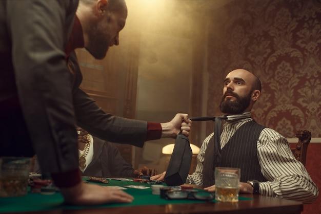 Gracz w pokera złapał krawat swojego przeciwnika, ostrzejszy w kasynie, ryzykował. uzależnienie od gier losowych. mężczyźni z whisky i cygarami w kasynie