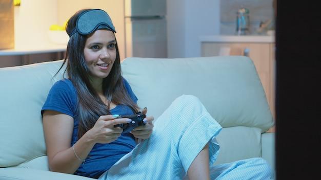 Gracz za pomocą joysticka, grając w gry wideo na konsoli, siedząc na kanapie w salonie. podekscytowana zdeterminowana kobieta korzystająca z kontrolera gamepad z klawiaturą do gier na playstation i bawiąca się wygrywając grę elektroniczną