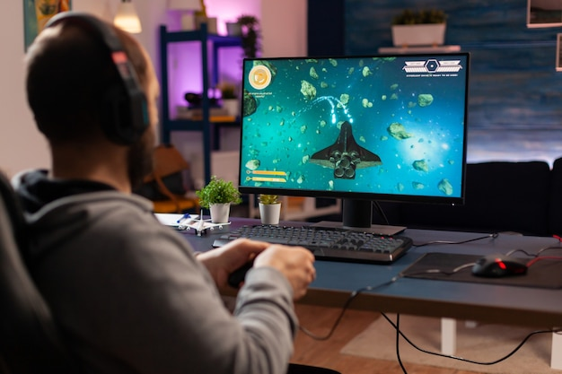 Gracz ze słuchawkami wykonujący grę wideo z nowoczesną grafiką na mistrzostwa kosmicznych strzelców. cyber przesyłania strumieniowego online podczas turnieju w grach przy użyciu technologii sieci bezprzewodowej