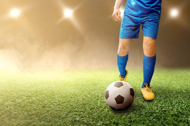 Gracza futbolu mężczyzna kopie piłkę na boisku piłkarskim