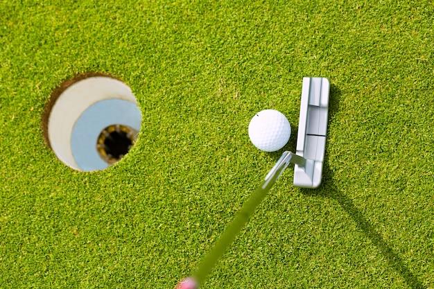 Gracza golfa kładzenia piłka w dziurze