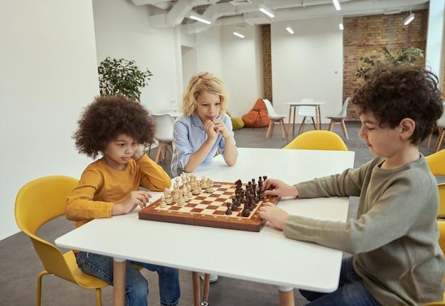 Gracze dzieci grają w szachy mali chłopcy siedzą przy stole i grają w szachowej szkole
