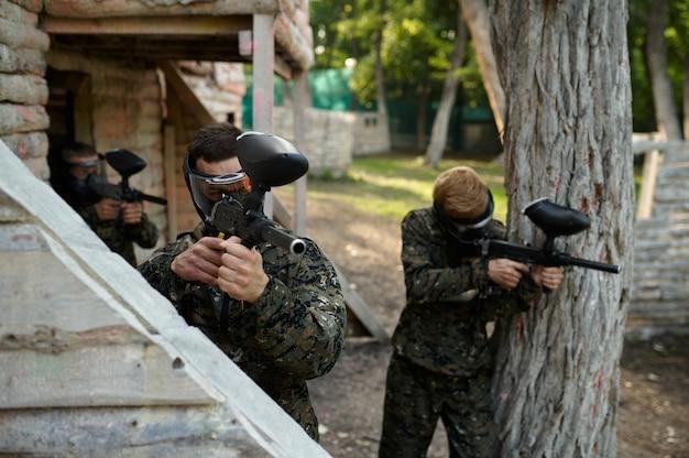 Gracze paintballa w mundurach i maskach strzelają z broni palnej na placu zabaw w lesie. sporty ekstremalne z bronią pneumatyczną i kulami lub markerami malarskimi, wojskowa gra zespołowa w plenerze, taktyka walki