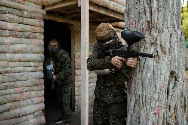 Gracze paintballa w mundurach strzelają z bronią