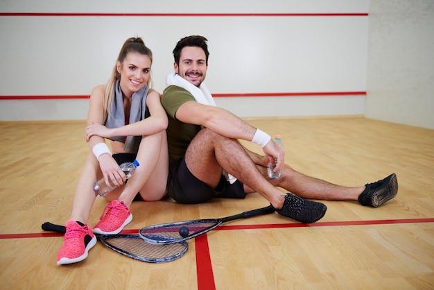 Gracze w squasha robiący sobie przerwę na parkiecie