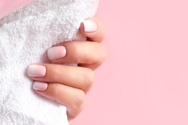 Gradientowy manicure i hands spa piękna kobieta zbliżenie dłoni wypielęgnowane paznokcie i miękka skóra dłoni piękne kobiety paznokcie z pięknym manicure różowym tle wyżu demograficznego skopiuj miejsce