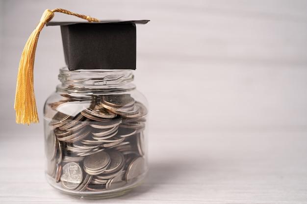 Graduation gap hat na monetach pieniądze w słoiku na fundusz edukacyjny