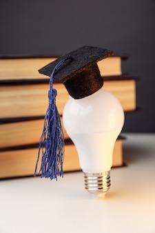 Graduation kapelusz na żarówce z książkami na stole. obraz pionowy. koncepcja edukacji.