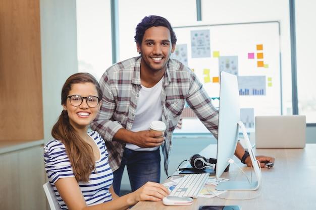 Graficy płci męskiej i żeńskiej pracujący w sali konferencyjnej