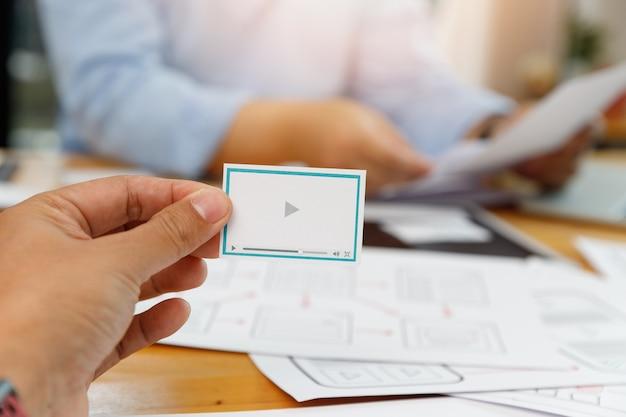 Graficy współpracują z projektantem ux ui, który planuje szablon układu aplikacji na telefon komórkowy komputer mobilny