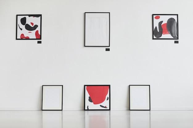 Graficzny obraz tła współczesnych abstrakcyjnych obrazów z czarno-czerwonymi wiszącymi na białej ścianie na wystawie w galerii sztuki,