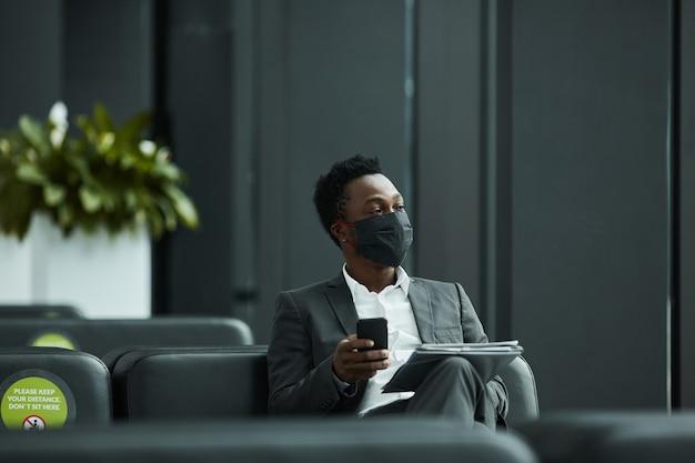 Graficzny portret afroamerykańskiego biznesmena noszącego maskę podczas pracy z laptopem w poczekalni na lotnisku z dystansem społecznym, miejsce kopiowania