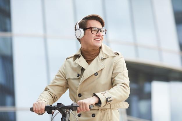 Graficzny portret do talii radosnego młodego biznesmena w płaszczu i słuchawkach, odwracającego wzrok podczas jazdy na skuterze elektrycznym ze szklanymi budynkami miejskimi w tle, kopia przestrzeń