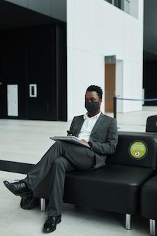 Graficzny portret pełnej długości afroamerykańskiego biznesmena noszącego maskę podczas pracy z laptopem w poczekalni na lotnisku z dystansem społecznym