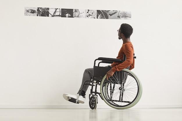Graficzny portret pełnometrażowy młodego afroamerykanina poruszającego się na wózku inwalidzkim i patrzącego na obrazy podczas zwiedzania wystawy w galerii sztuki współczesnej,