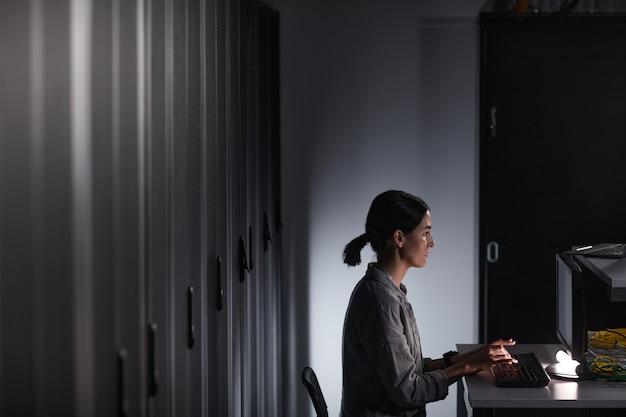Graficzny widok z boku portret kobiety inżyniera sieci korzystającej z komputera podczas pracy w ciemnej serwerowni, kopia przestrzeń
