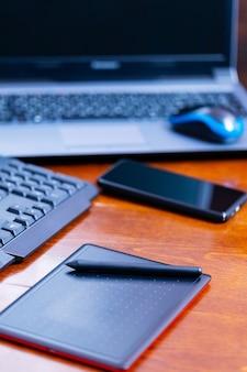 Grafik do pracy zdalnej. miejsce pracy freelancera. laptop, smartfon i tablet graficzny w miejscu pracy