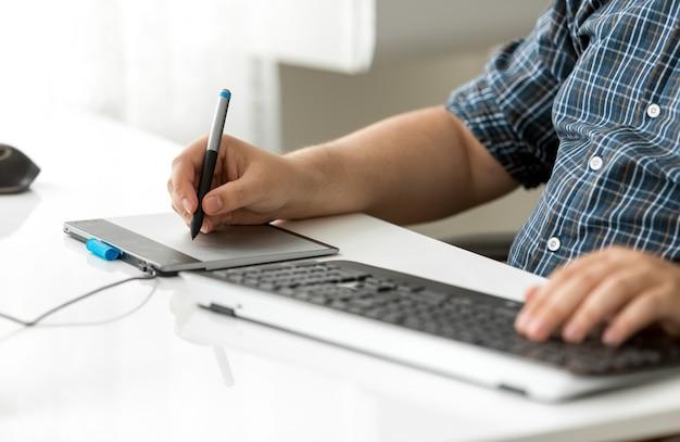 Grafik korzystający z cyfrowego tabletu w biurze