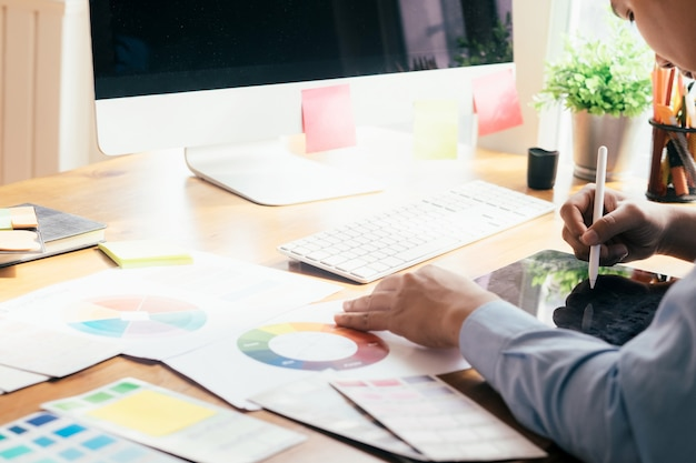 Grafik pracujący na komputerze i używanym tablecie graficznym.