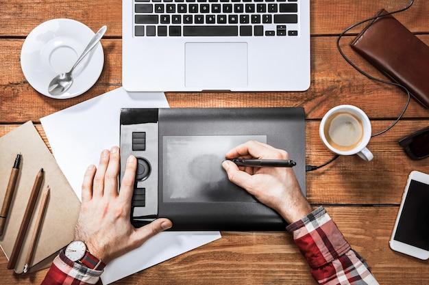 Grafik pracujący z interaktywnym ekranem piórkowym, cyfrowym tabletem do rysowania i piórem na komputerze. widok z góry