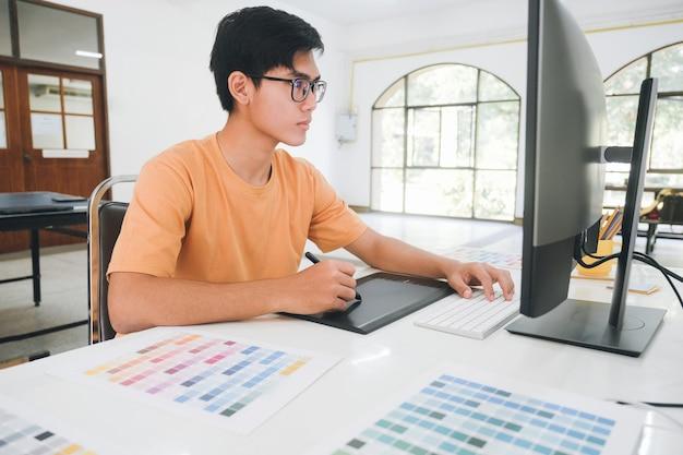 Grafik pracujący z próbkami kolorów do wyboru. grafik w pracy. próbki kolorów. młody fotograf i grafik w pracy biurowej.