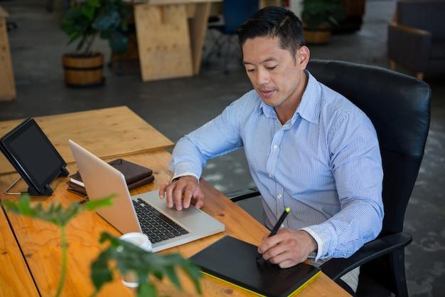 Grafik rysujący na tablecie graficznym podczas korzystania z laptopa