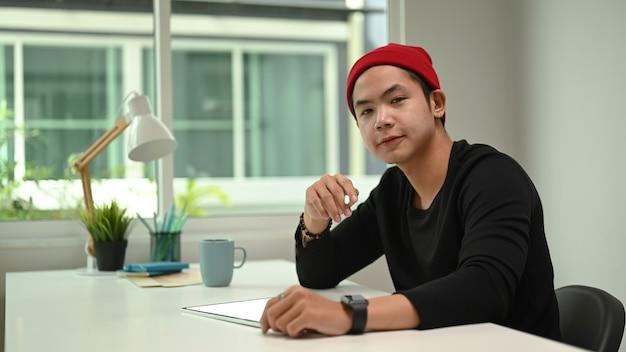 Grafik w czerwonym wełnianym kapeluszu pracuje na cyfrowym tablecie i patrząc na kamery, siedząc w swoim miejscu pracy.