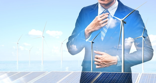 Grafika podwójnej ekspozycji ludzi biznesu pracujących nad farmą turbin wiatrowych i interfejsem pracownika zielonej energii odnawialnej