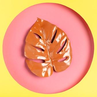 Grafika z geometrycznym kształtem papieru i liściem