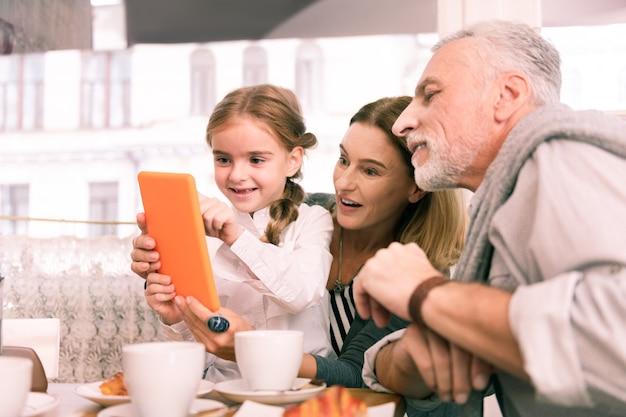 Graj na tablecie. ciemnooka wnuczka grająca na pomarańczowym tablecie siedzi obok dziadków