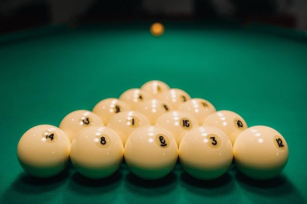 Grają w bilard na zielonym stole, kulki układane są w trójkąt na stole.